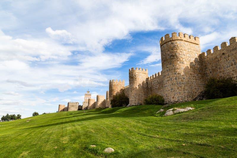 Vue des murs médiévaux de ville entourant la ville d'Avila, de l'Espagne, et de la pelouse verte devant Puerta del Carmen image libre de droits