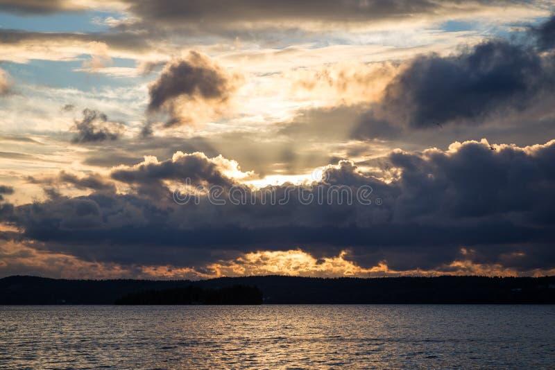 Vue des nuages foncés et dramatiques, des rayons de soleil et d'un lac image stock