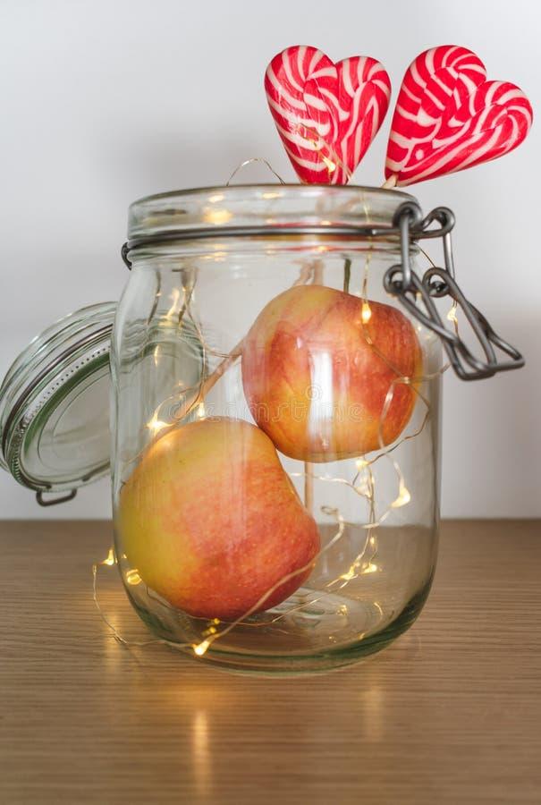 Vue des pommes et des lucettes dans un pot avec des lumières de Noël photographie stock libre de droits