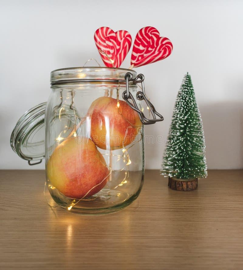 Vue des pommes et des lucettes dans un pot avec des lumières de Noël et une figurine d'arbre photographie stock