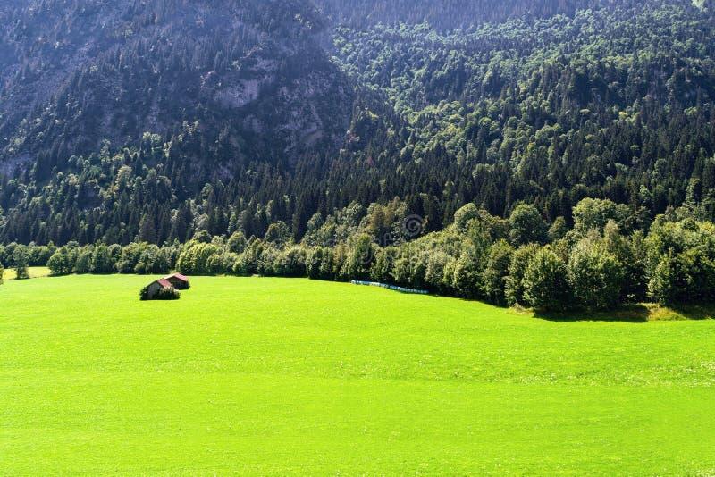 Vue des prés alpins bien-toilettés avec des annexes contre le contexte des montagnes photos stock