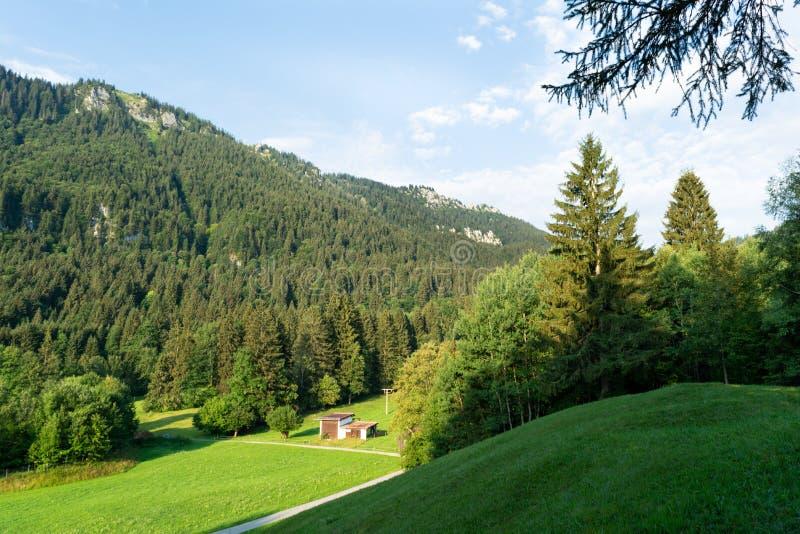 Vue des prés alpins bien-toilettés avec des annexes et de la route s'étendant dans la distance photographie stock libre de droits