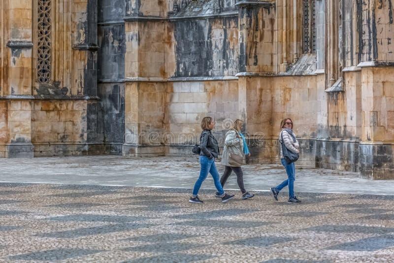 Vue des touristes de femmes marchant sur l'extérieur près de la façade extérieure gothique du monastère de Batalha, Mosteiro DA B image libre de droits