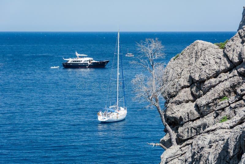 Vue des yachts, des roches et de la baie photo stock