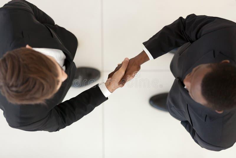Vue directement en haut des hommes d'affaires divers dans les costumes se serrant la main image libre de droits