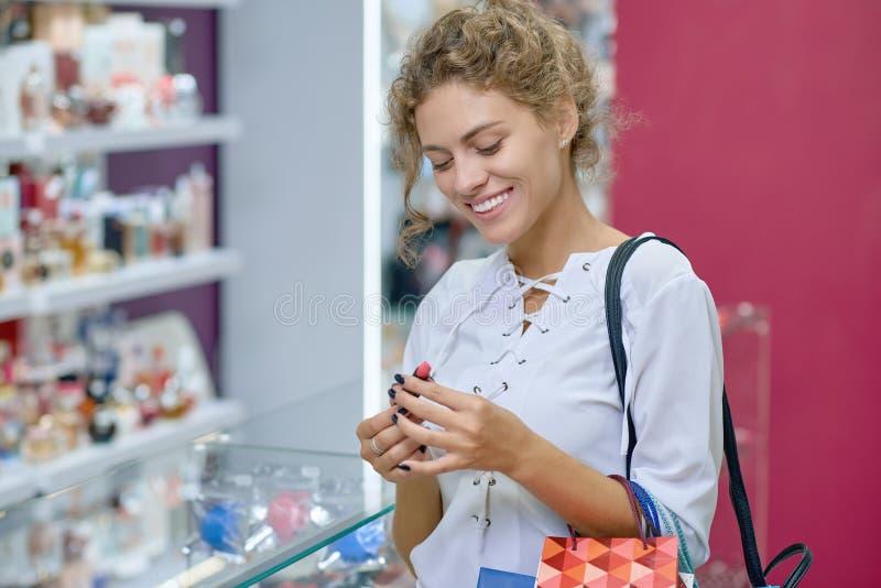 Vue du côté du client attirant choisissant le nouveau rouge à lèvres dans le magasin photographie stock libre de droits
