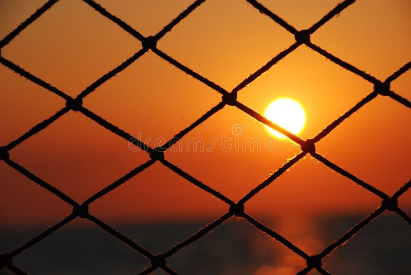 Vue du coucher du soleil par le filet du voilier photo libre de droits