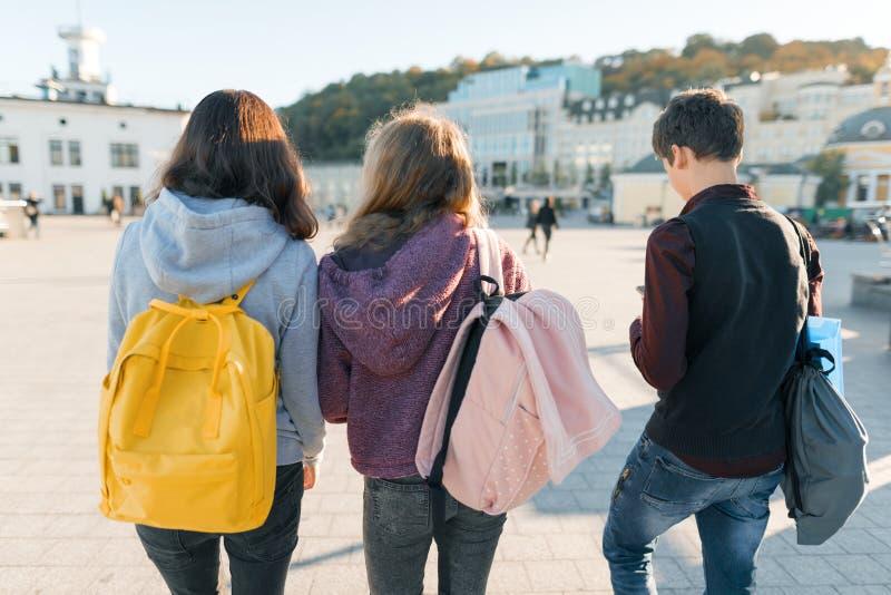 Vue du dos sur trois étudiants de lycée Fond de ville, heure d'or images stock