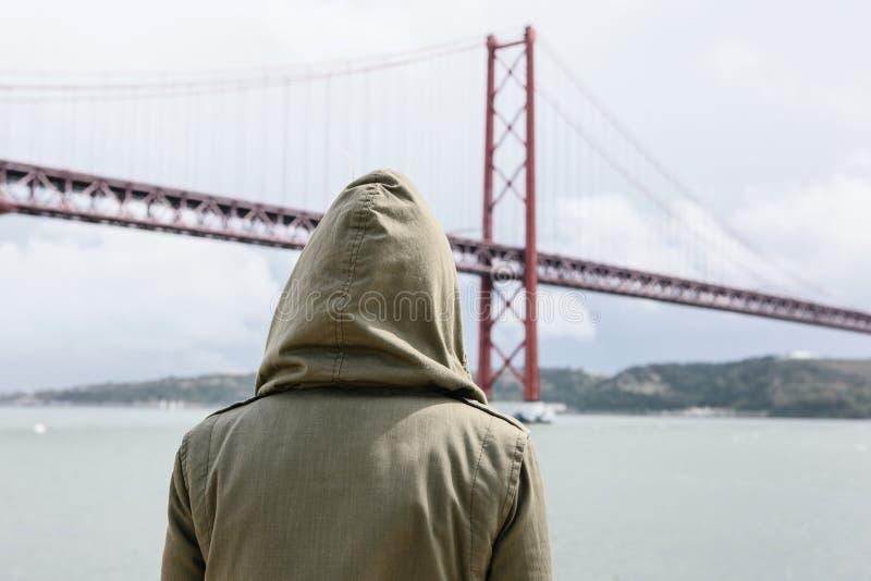 Vue du dos Une fille dans un capot par temps venteux regarde une belle vue du pont photographie stock