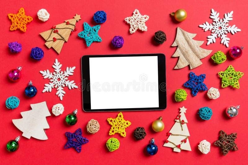 Vue du haut de la tablette numérique sur fond rouge faite de décorations et de jouets de vacances Concept d'ornement de Noël photographie stock libre de droits