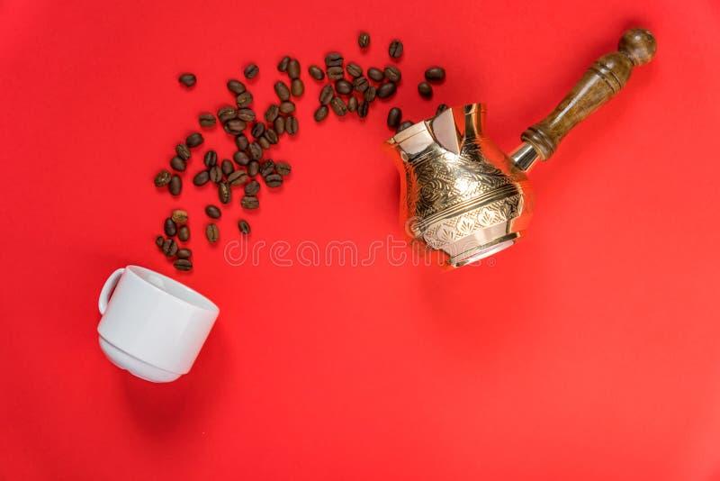 Vue du haut des haricots de café dans la casserole traditionnelle turque, tasse blanche sur fond rouge photos stock