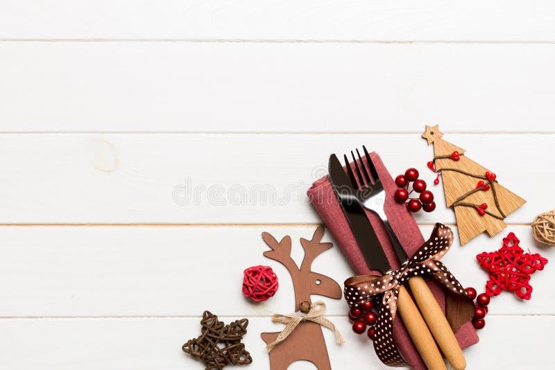 Vue du haut des ustensiles du nouvel an sur la serviette avec décoration de vacances et rennes sur fond de bois Concept de dîner  photographie stock libre de droits