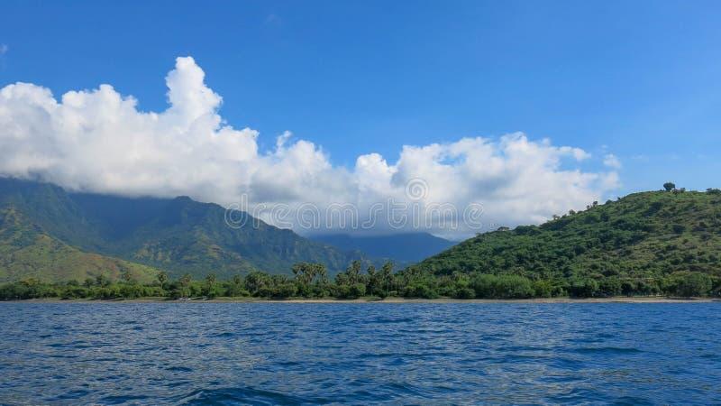 Vue du niveau de la mer sur la côte pittoresque d'une île tropicale Chaîne de montagne dans la distance avec la légère opacité images stock