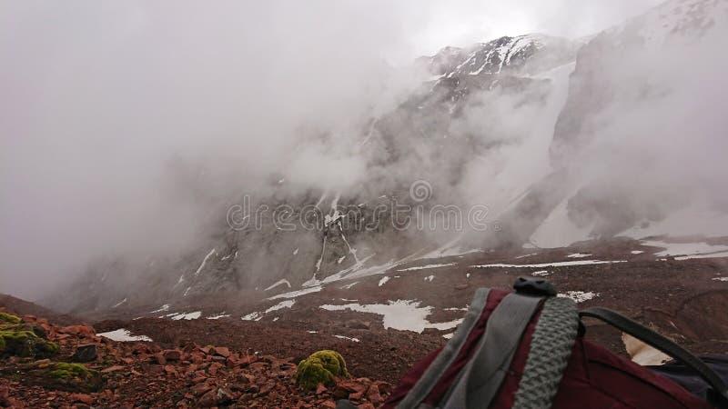 Vue du sac à dos de courroie dans les montagnes Les nuages dérivent la neige passée est évident sur les pentes de montagne photographie stock libre de droits