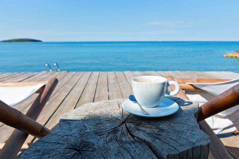 Vue en bois de plancher et de mer avec les chaises longues et le café photo stock