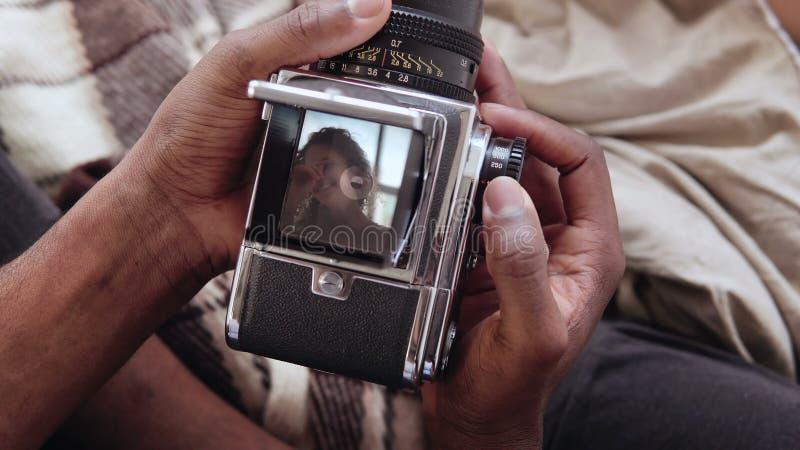 Vue en gros plan d'homme africain tenant le vieux photocamera, prenant à portrait de photo la belle femme Couples multiraciaux su photo libre de droits