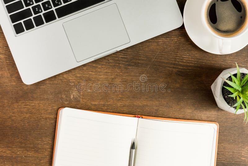 Vue en gros plan d'ordinateur portable, de carnet vide et de tasse de café sur le dessus de table en bois image libre de droits