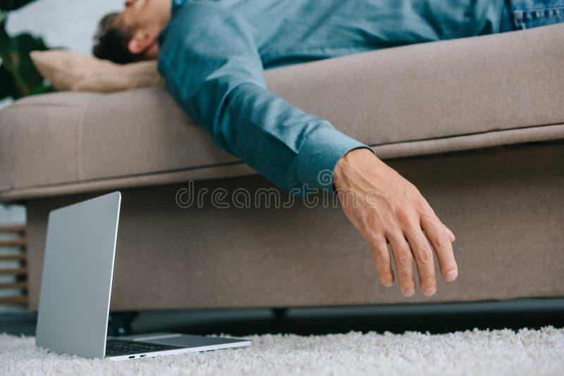 vue en gros plan d'ordinateur portable sur le tapis et l'homme malade image stock