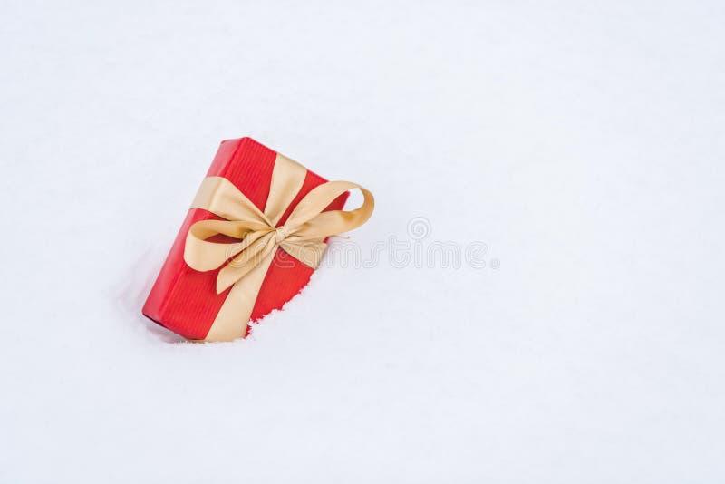 vue en gros plan de boîte-cadeau rouge avec le ruban d'or dans la neige photo libre de droits