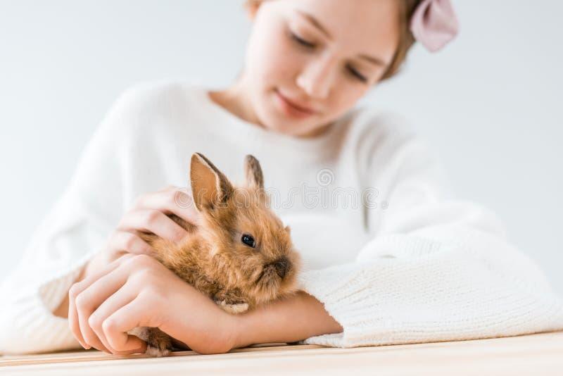 Vue en gros plan de fille de sourire tenant le lapin velu adorable image libre de droits