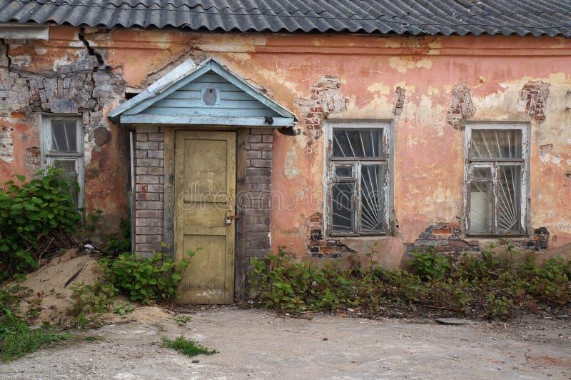 Vue en gros plan de la façade d'une vieille maison abandonnée Porte d'entrée en bois, fenêtres, murs de briques plâtrés minables photographie stock libre de droits