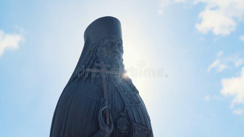 Vue en gros plan de la statue en bronze ou en pierre du prêtre avec la croix dans sa main dans le jour ensoleillé contre le ciel  image stock