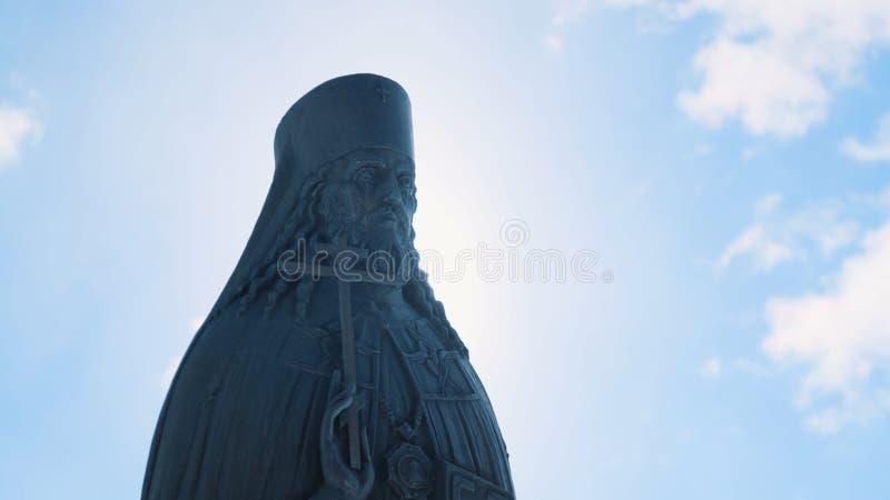 Vue en gros plan de la statue en bronze ou en pierre du prêtre avec la croix dans sa main dans le jour ensoleillé contre le ciel  photos stock