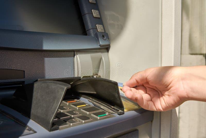 Vue en gros plan de main du ` s de distributeur automatique de billets et de femme avec la carte de crédit photo libre de droits