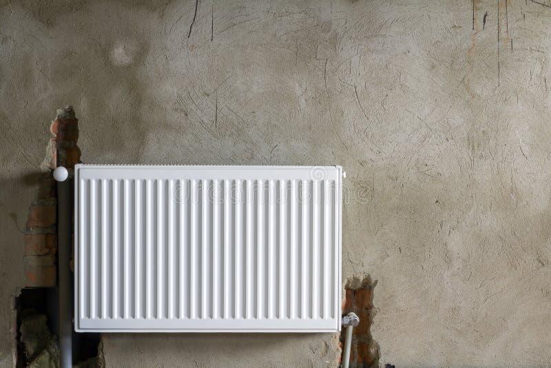 Vue en gros plan de nouveau radiateur de chauffage installé d'isolement sur le mur plâtré rugueux de brique dans une salle vide d photo stock
