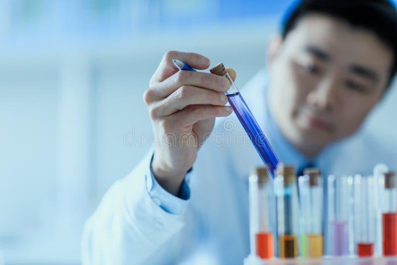 Vue en gros plan de scientifique asiatique dans le manteau de laboratoire tenant le tube à essai avec du réactif images libres de droits
