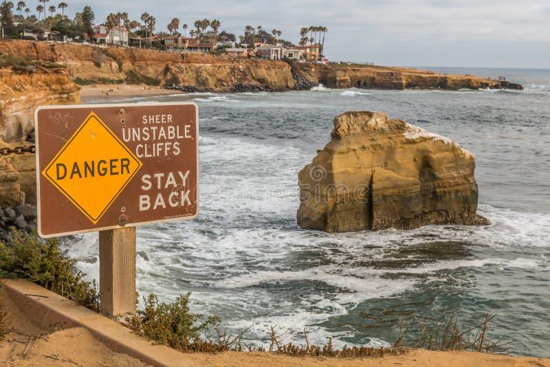 Vue en gros plan de signe de danger aux falaises de coucher du soleil images libres de droits