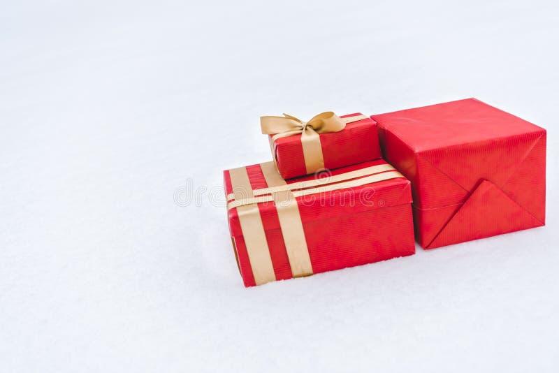 vue en gros plan des boîte-cadeau rouges enveloppés avec les rubans d'or sur la neige images libres de droits