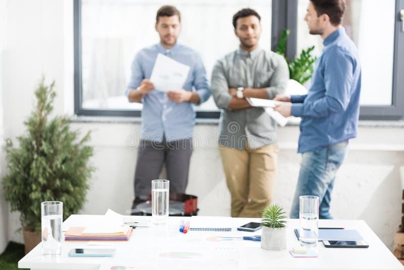Vue en gros plan des documents et des graphiques de gestion sur le bureau et des hommes d'affaires se tenant derrière images libres de droits