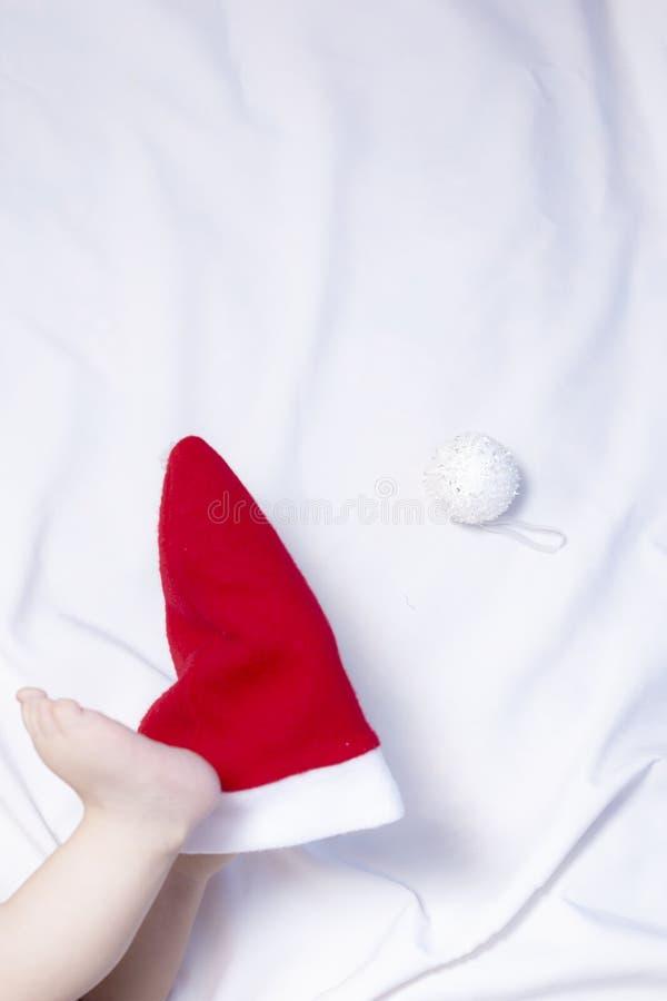 Vue en gros plan des jambes du bébé garçon sur le chapeau rouge de Santa Claus Premier Noël d'un bébé nouveau-né photos stock