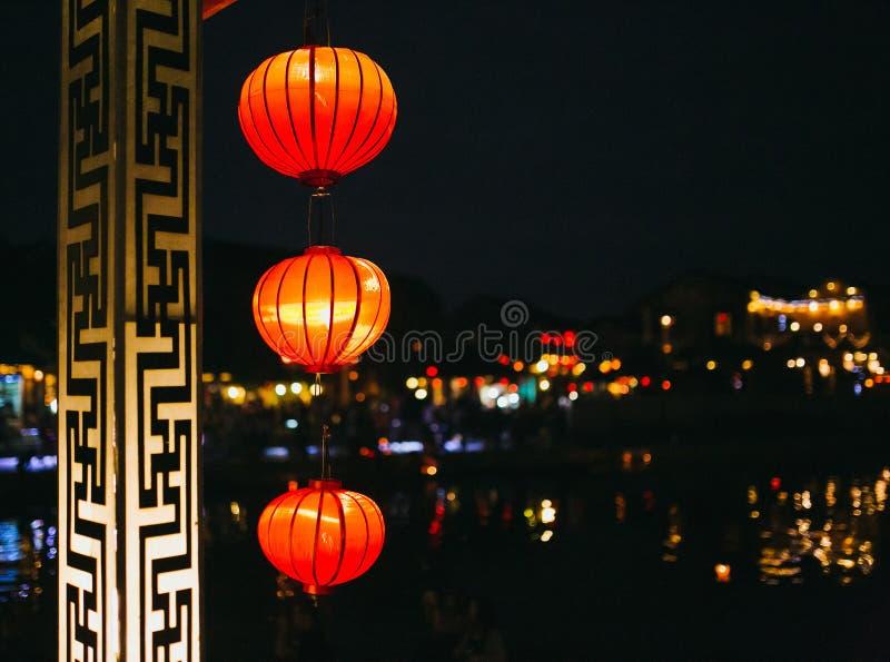 vue en gros plan des lanternes rouges lumineuses et du paysage urbain brouillé, Hoi images stock