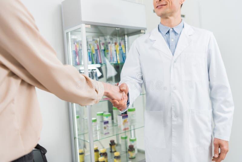 Vue en gros plan du docteur et du patient féminin se serrant la main dans moderne photo stock