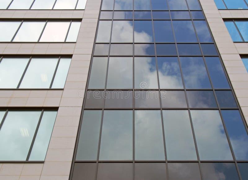 vue en hauteur sur la façade d'un immeuble de bureaux moderne au ciel bleu et aux nuages blancs reflétés dans les rangées de f photo libre de droits