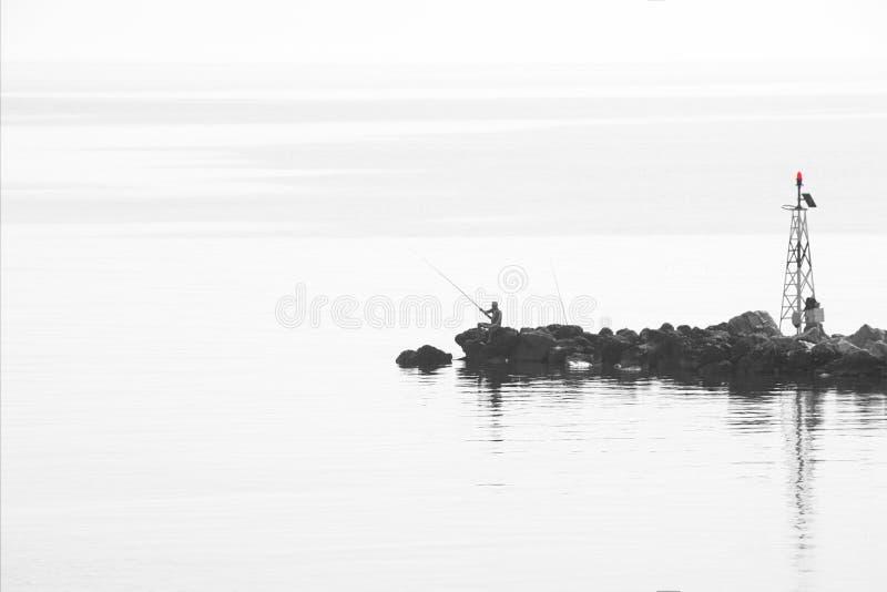 Vue en temps et brume de début de la matinée Silhouette de l'esprit de pêcheur images libres de droits