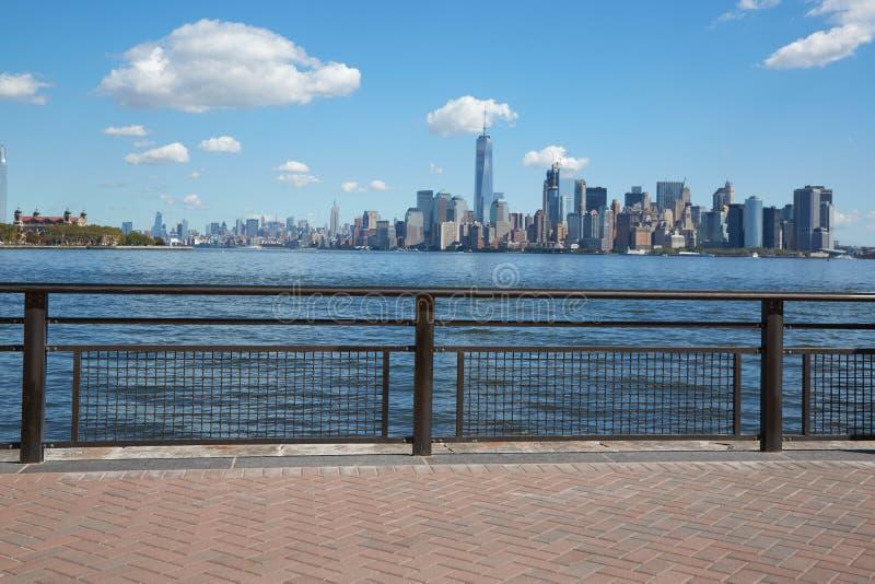 Vue et Ellis Island d'horizon de New York City de terrasse de dock photographie stock libre de droits