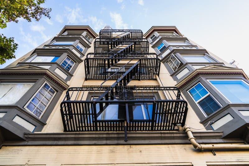 Vue extérieure de l'immeuble résidentiel multifamilial; Les anciens escaliers de secours en métal accrochés au côté du bâtiment ; photo stock