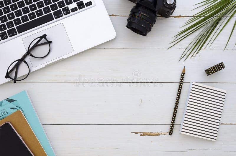 Vue faite d'ordinateur portable, lunettes, palmette et carnet sur le fond en bois blanc Maquette plate d'affaires de configuratio photo libre de droits