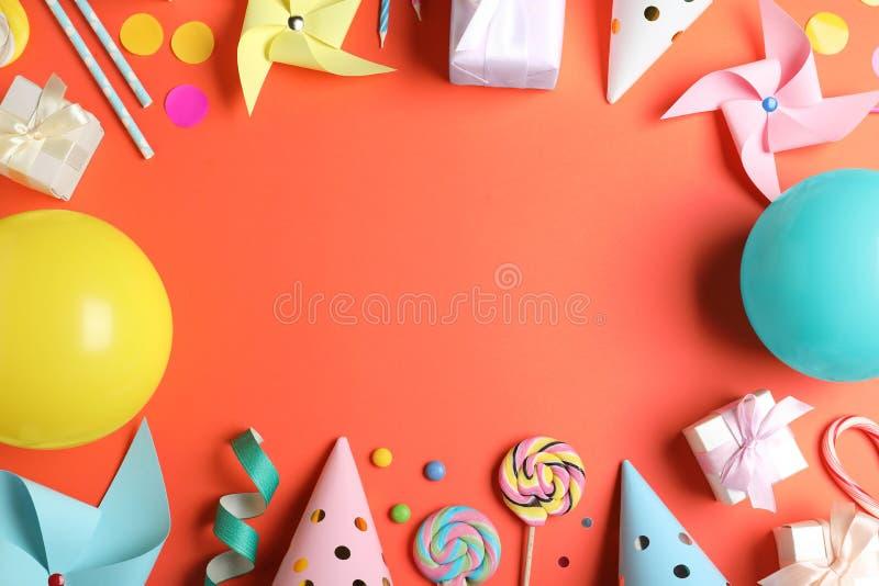 Vue faite de différents articles de fête d'anniversaire sur le fond de corail, configuration plate photos libres de droits