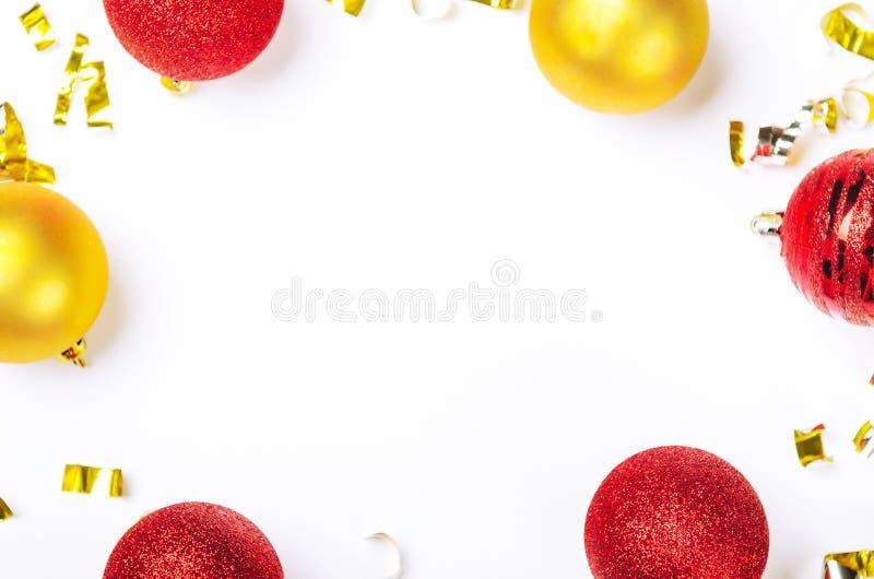 Vue faite de jouets de Noël avec rouge et d'or et confettis d'aluminium sur le fond blanc Endroit pour l'inscription photos stock