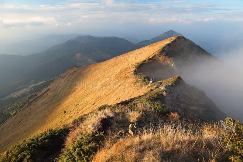 Vue fascinante au paysage avec de hautes montagnes, brouillard, rochers rocheux, pelouse avec l'herbe jaune, ciel nuageux le jour images stock