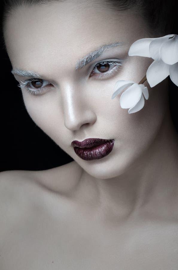 Vue frontale de maquillage artistique de portrait de beauté, lèvres de Bourgogne, visage, près de la fleur blanche, d'isolement s image stock