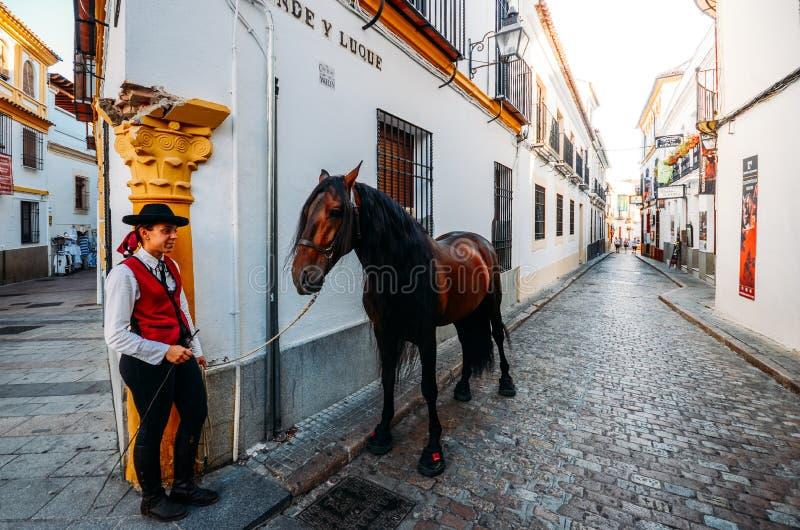 Vue grande-angulaire de femme posant à côté d'un beau cheval au quart juif du ` s de Cordoue, qui a été déclaré un monde photo libre de droits