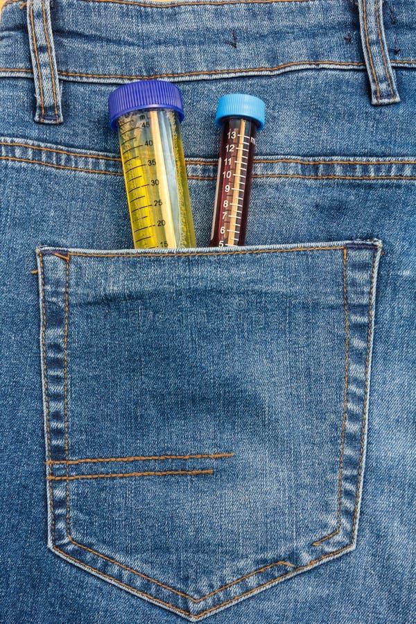 Vue haute ?troite au tube ? essai avec l'urine et sang collant d'une poche de blues-jean photo stock