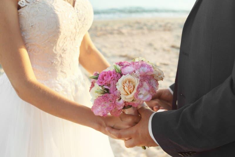 Vue haute étroite d'épouser des couples tenant le bouquet image libre de droits