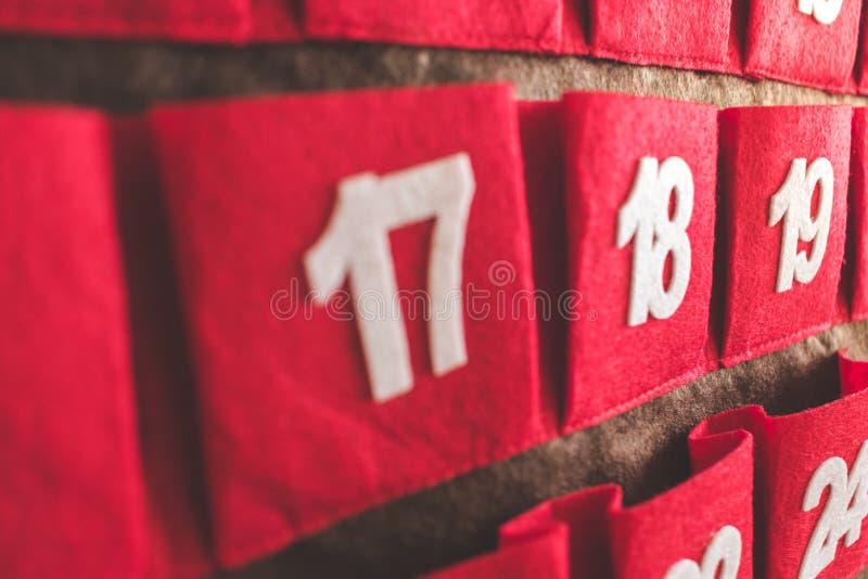 Vue haute étroite d'un calendrier rouge et brun d'avènement de textile avec des dates photographie stock