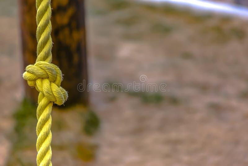 Vue haute étroite d'une corde jaune nouée avec la saleté sur la surface image stock